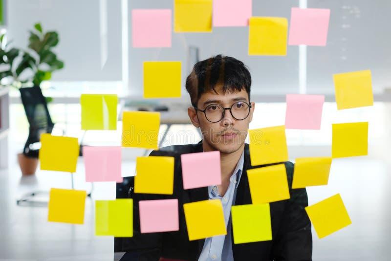 认为年轻亚洲的商人,当读稠粘的笔记在办公室,群策群力创造性的飞行的想法的事务对成功时 免版税库存图片
