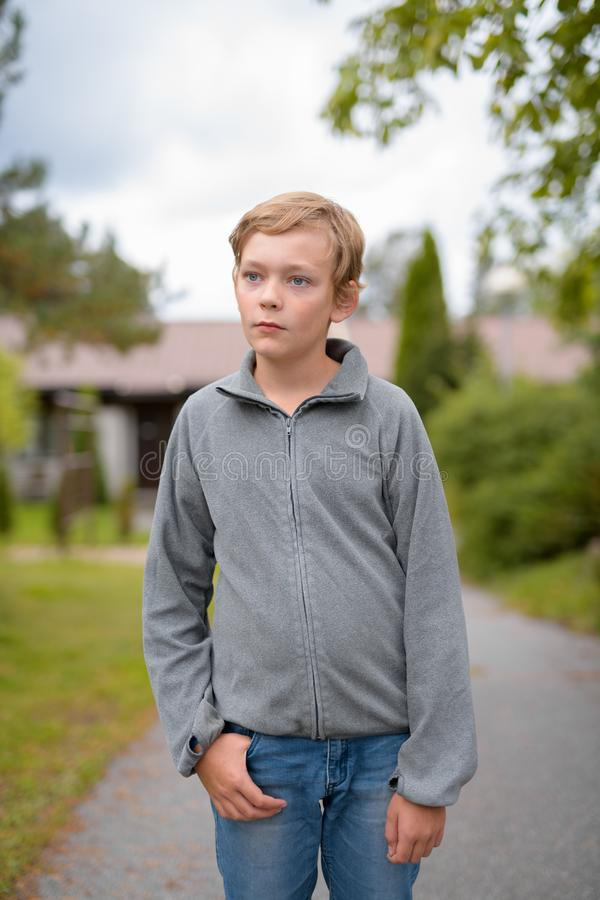 认为年轻白肤金发的帅哥,当在家站立户外时 免版税图库摄影