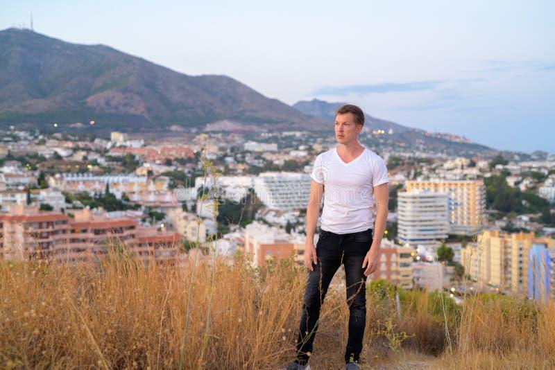 认为年轻英俊的旅游的人,当站立在小山顶部时 免版税库存图片