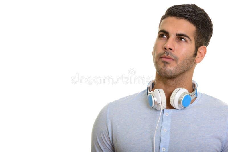认为年轻英俊的波斯的人,当佩带耳机aro时 库存照片