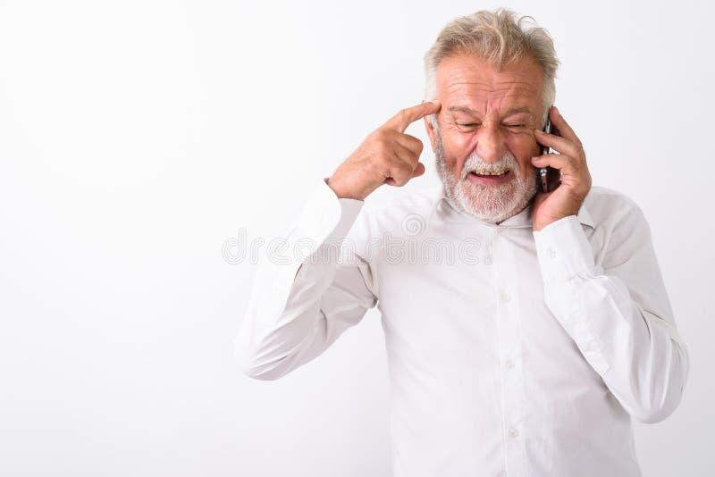 认为恼怒的资深有胡子的人,当谈话在电话时 库存图片