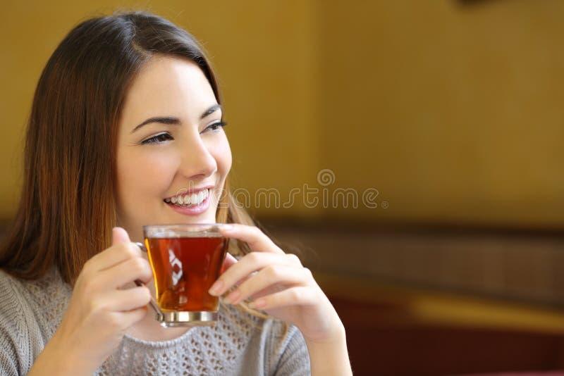 认为愉快的妇女拿着一杯茶在咖啡店的 免版税库存照片