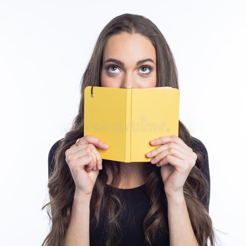 认为拿着黄色笔记本的少妇画象  免版税库存照片