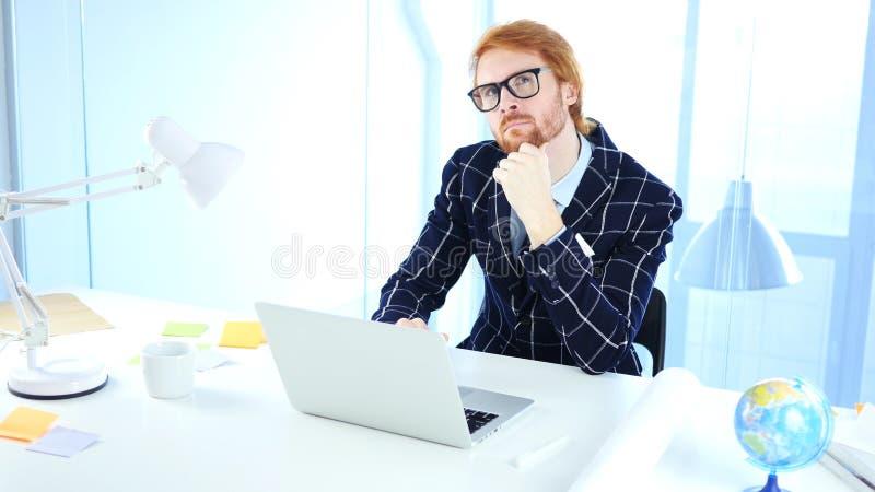 认为新的想法的沉思红头发人商人在工作,创造性的设计师 库存照片