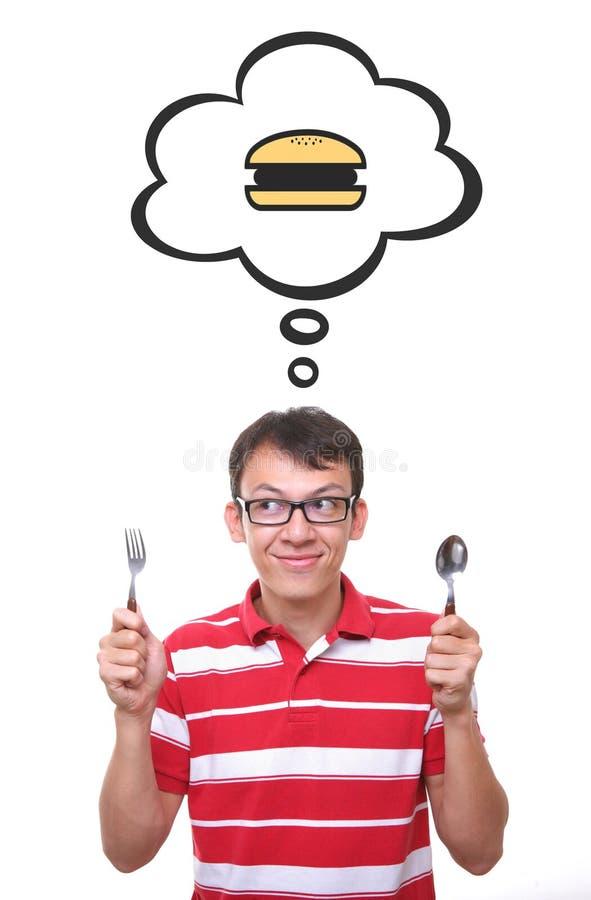 认为汉堡包的饥饿的年轻人 免版税库存照片