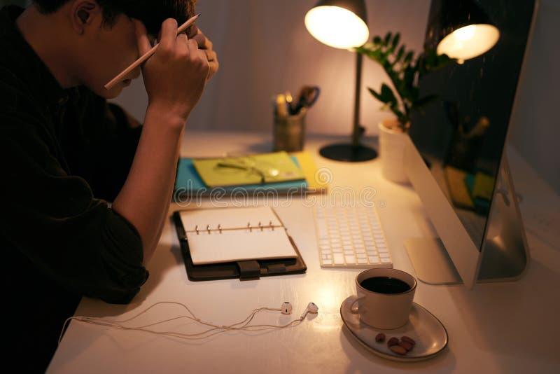 认为的商人,当坐在他运转的书桌时 免版税图库摄影