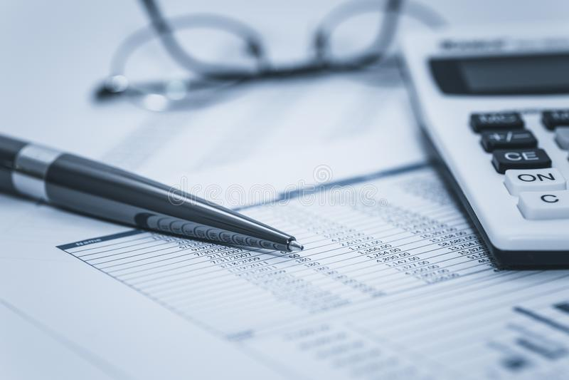 认为的财政辩论术验核银行银行帐户股票与玻璃笔和计算器的报表数据在被洗涤的蓝色 图库摄影