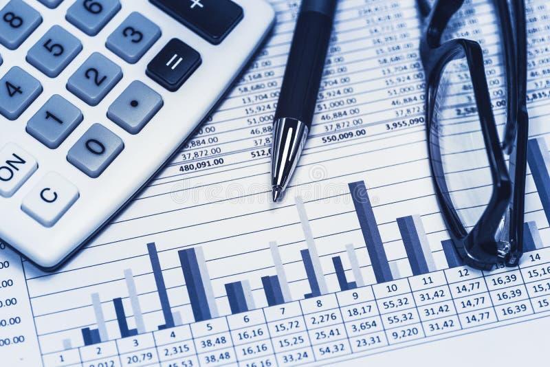 认为的财政银行银行业务银行家帐户库存报表数据与玻璃笔和计算器在蓝色 免版税库存图片