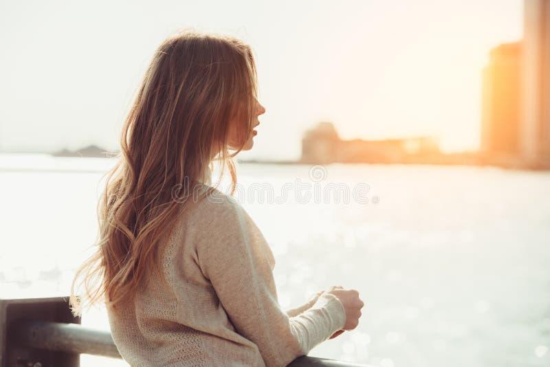 认为美丽的孤独的女孩作梦和,当等待在城市海洋码头的日期在日落时间时 图库摄影