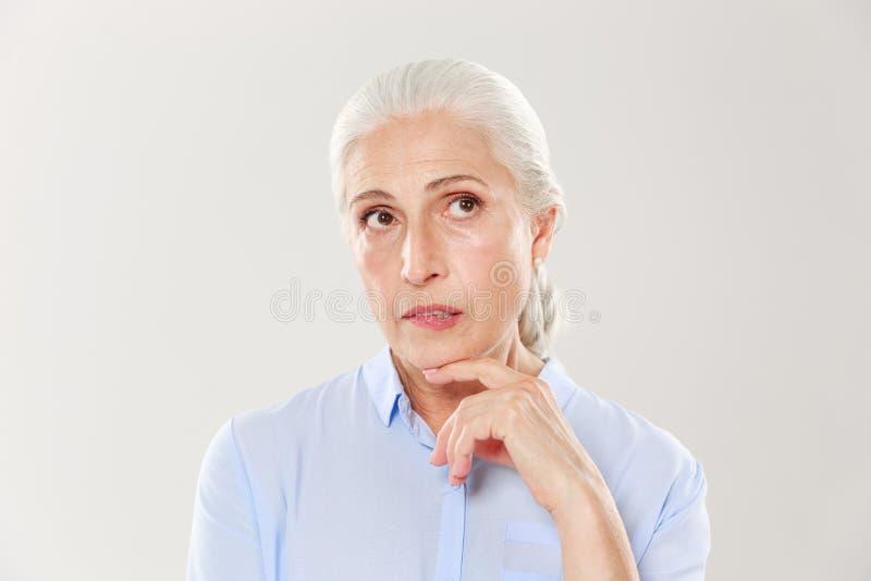 认为蓝色衬衣的美丽的老妇人特写镜头,看 免版税图库摄影