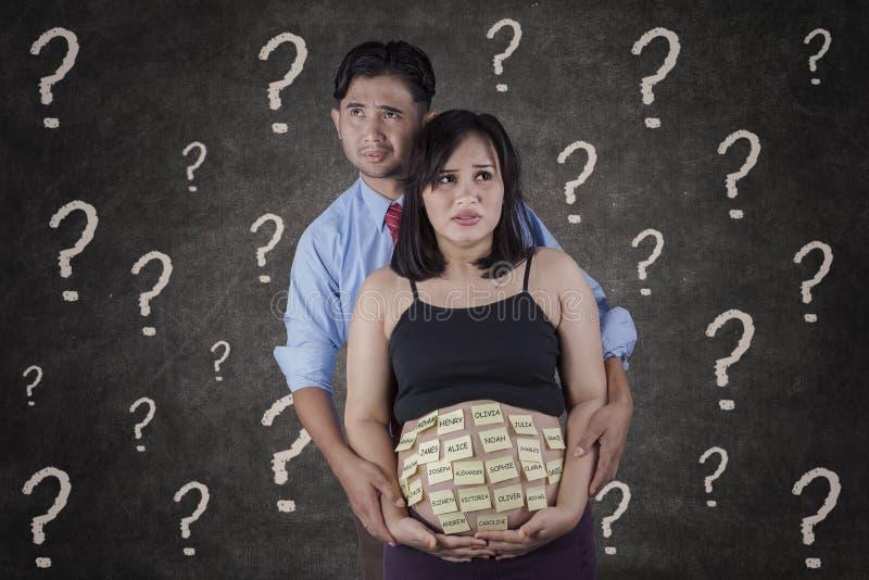 认为婴孩名字的亚裔父母 免版税库存图片