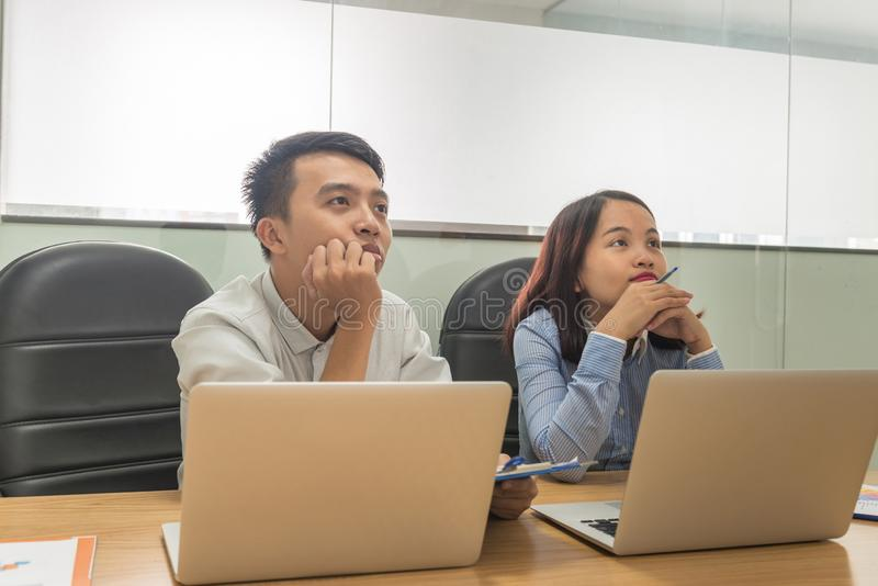 认真听在见面的年轻亚裔雇员 免版税库存图片