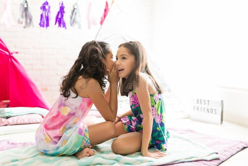 认真听闲话的女孩在鸭绒垫子在微睡零件期间 免版税库存照片