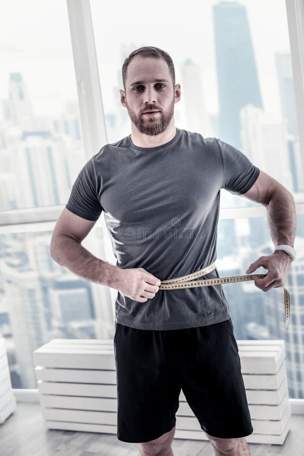 认真英俊的运动员测量的腰部 库存图片