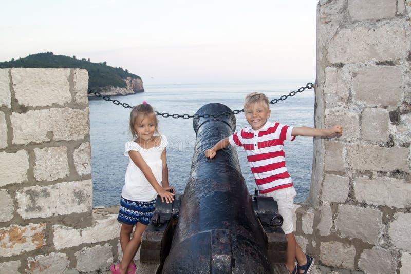 认知休闲的概念与孩子的 有一个女孩身分的愉快和微笑的男孩在城市墙壁上的一门老大炮附近 库存图片