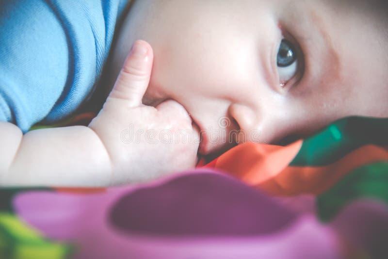 讨人喜欢的矮小的婴孩说谎的特写镜头 免版税库存图片