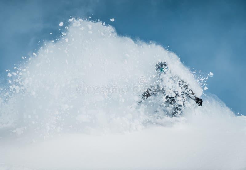 讨便宜者的滑雪者下降山根据早晨太阳 免版税库存图片