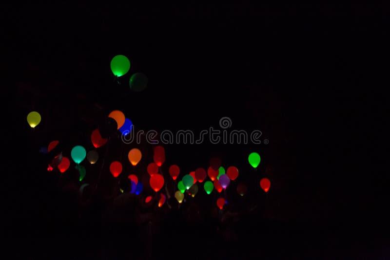 让五颜六色的人们,发光的气球在黑暗的夜空飞行 免版税库存照片