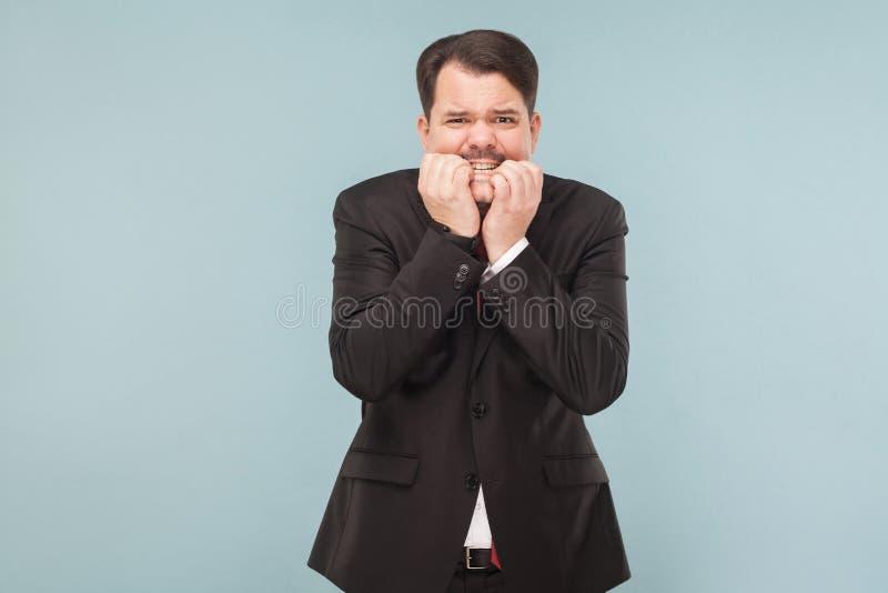 让商人叮咬担心他的钉子以兴奋 免版税库存图片