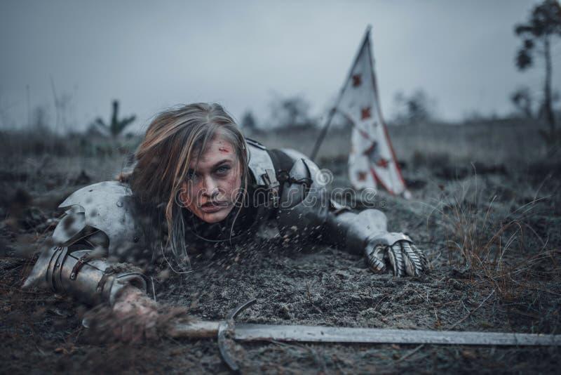 让娜d在装甲的`弧的图象的女孩在与剑的泥爬行在她的在旗子背景的手上  免版税库存图片