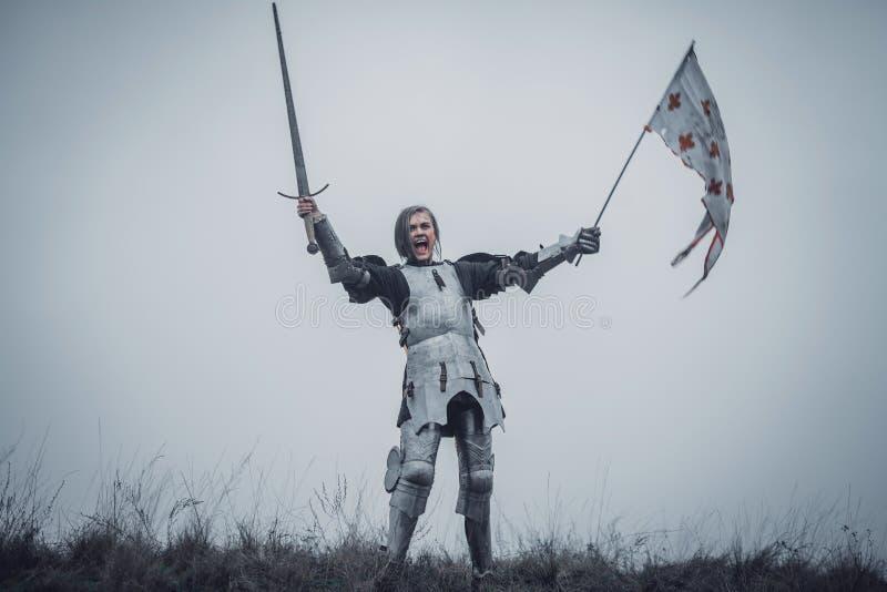 让娜d `在装甲和问题标语的弧立场的图象的女孩与被上升的剑和旗子在她的手上 库存图片