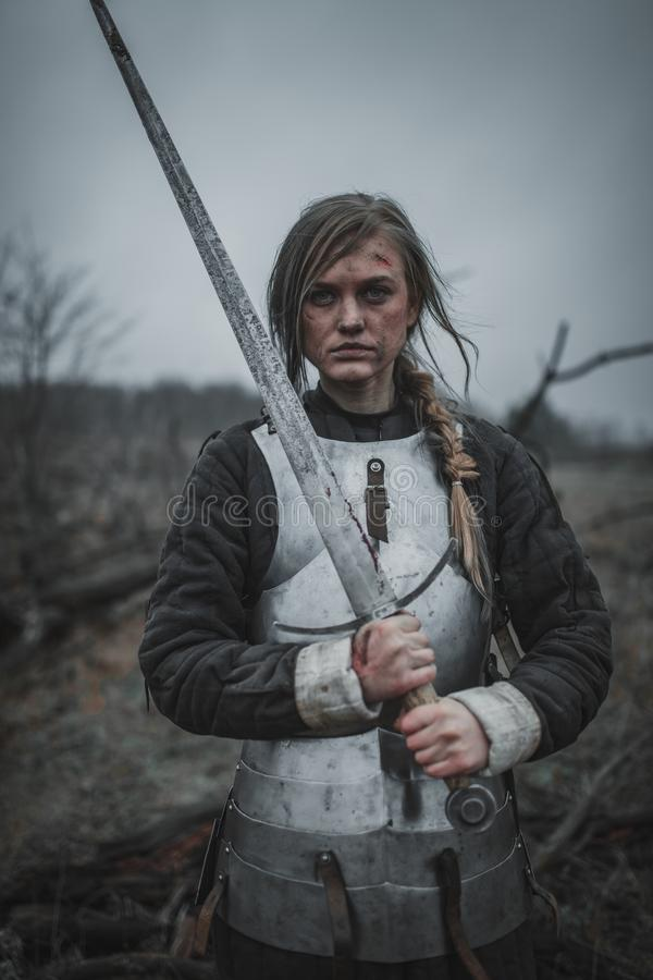 让娜d `弧的图象的女孩在装甲和与剑在她的手上在草甸站立 回到视图 免版税库存照片