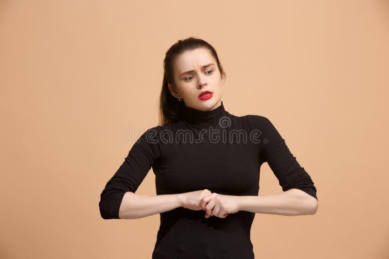 让我认为 有做出选择的周道的表示的半信半疑的沉思妇女反对淡色背景 免版税库存图片