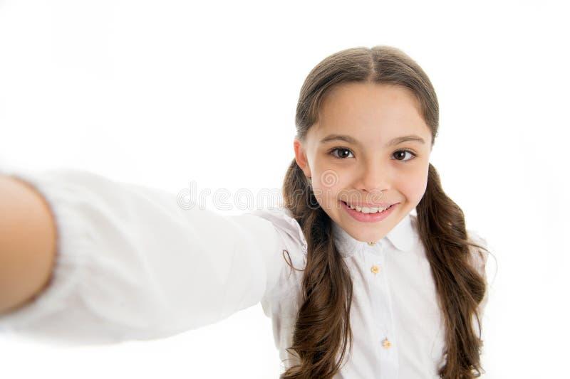 让我采取selfie 儿童女孩校服穿衣的拿着智能手机拍照片 儿童愉快校服的孩子 免版税库存图片
