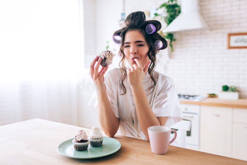 让烦恼的不快乐的年轻女人吃与奶油的薄煎饼在上面 漏的手指 杯和薄煎饼在桌上 单独在厨房里 库存图片