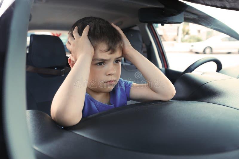 让烦恼的小男孩被关闭在汽车里面 免版税库存照片