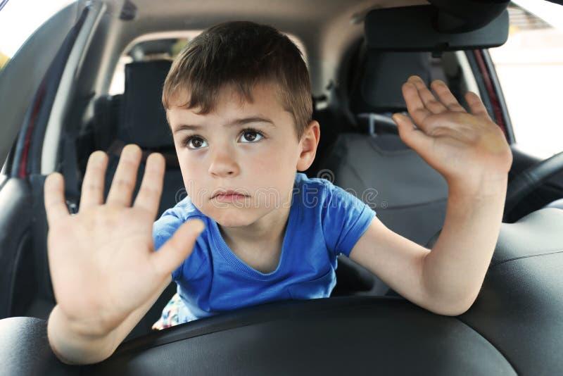 让烦恼的小男孩被关闭在汽车里面 图库摄影