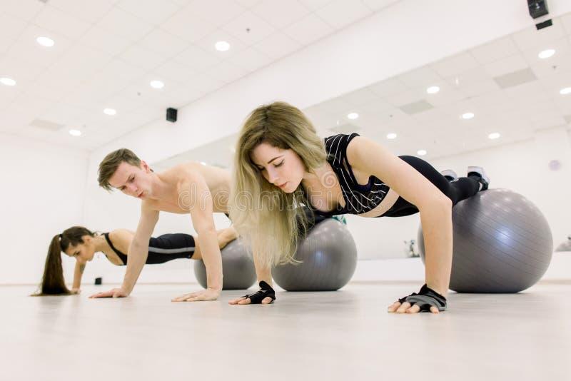 训练与在健身房的fitballs的人 免版税库存图片