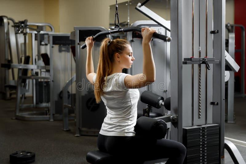 训练单独她的身体在健身房的女孩 免版税库存照片