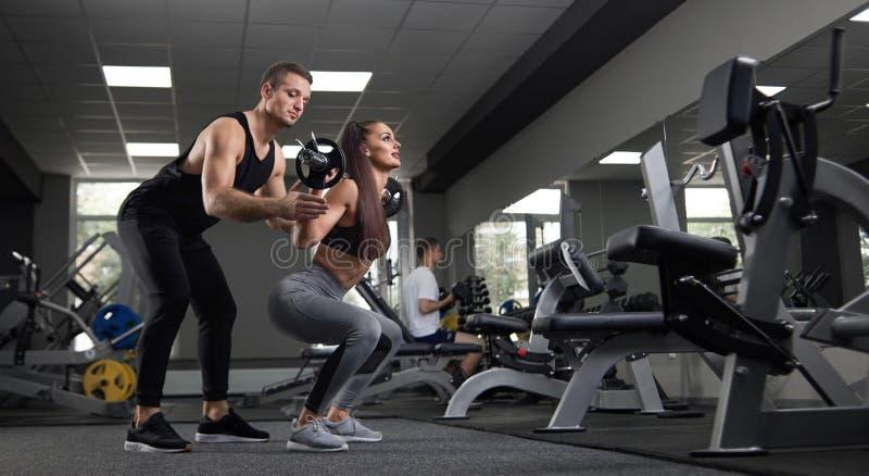 训练在健身房的两年轻人画象  免版税图库摄影