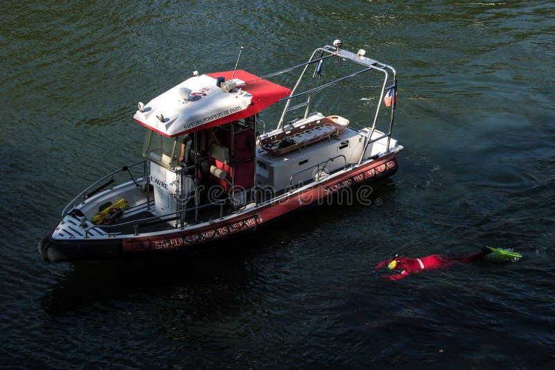 训练在河塞纳河的巴黎人消防队员 被淹没的水肺成套装备的一个人在水面下 库存照片