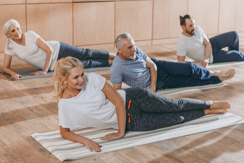 训练在瑜伽席子的微笑的资深人民 库存图片