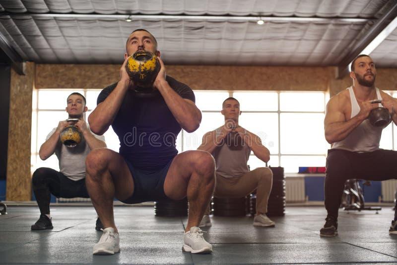 训练在Crossfit健身房的不同种族的小组男性运动员 库存图片