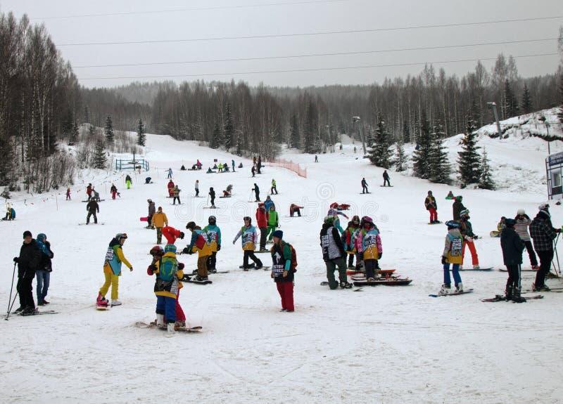 训练挡雪板和滑雪者障碍滑雪的儿童的小组 雪板运动和滑雪当青年时尚 库存照片