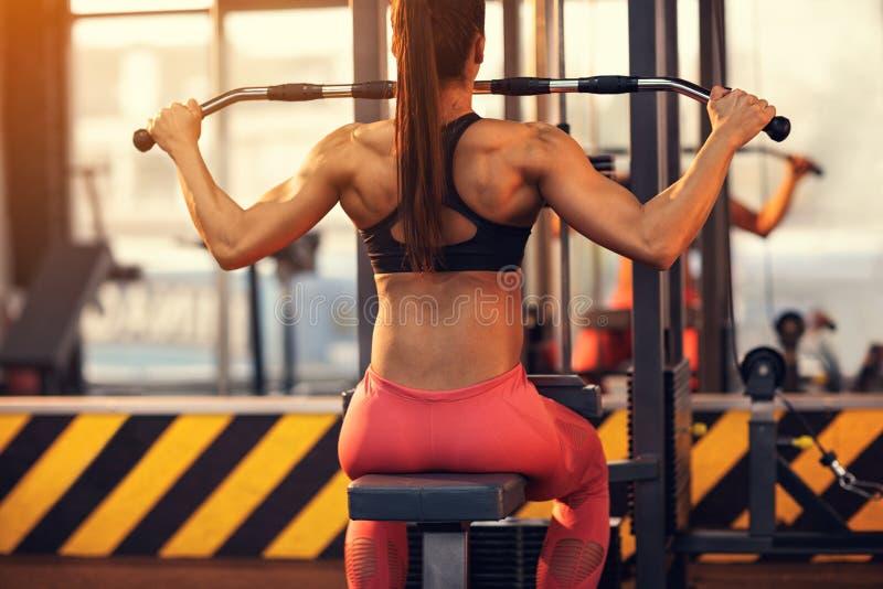 训练的在健身房,后面看法爱好健美者女性 免版税图库摄影