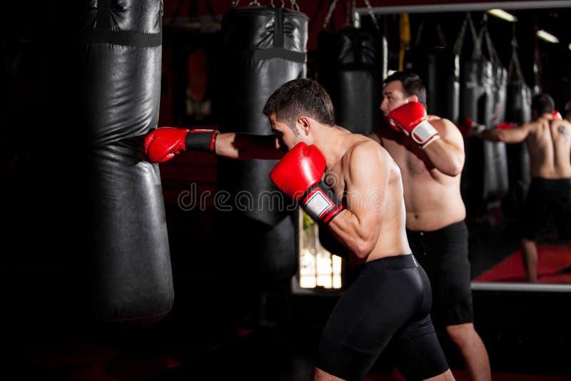 训练与一个沙袋的拳击手 免版税库存照片