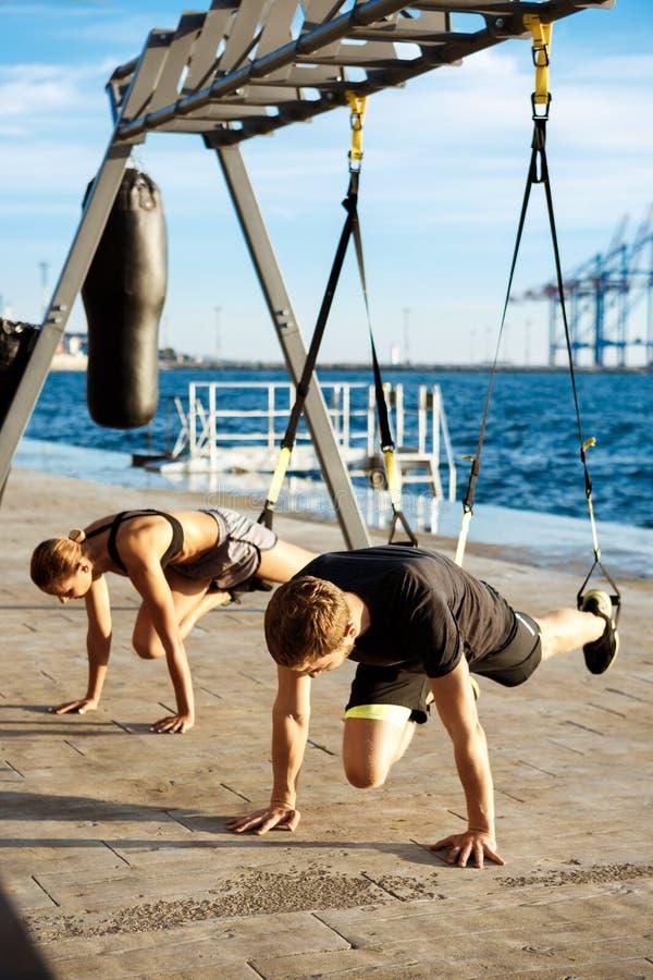 训练与trx的年轻嬉戏人民在海附近早晨 库存图片