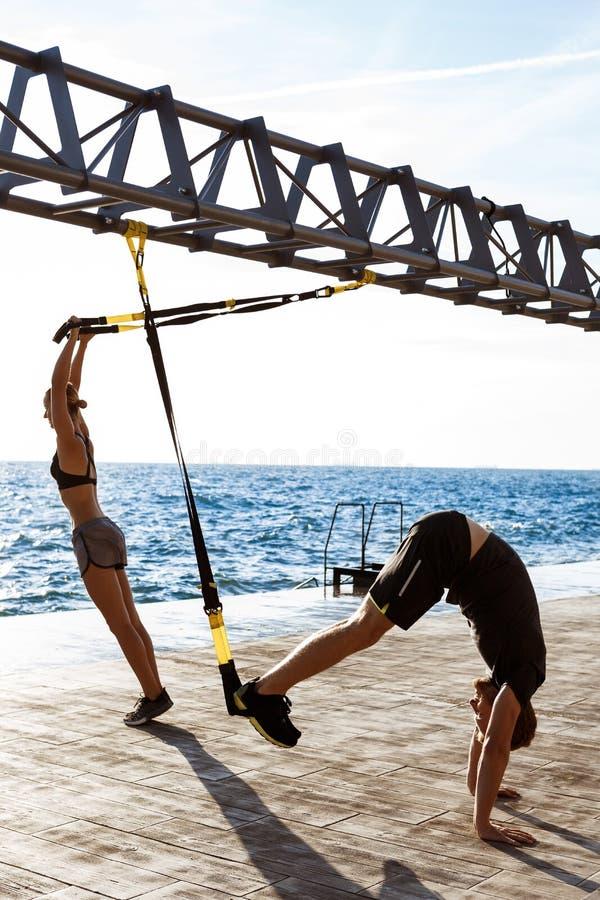 训练与trx的年轻嬉戏人民在海附近早晨 免版税库存照片
