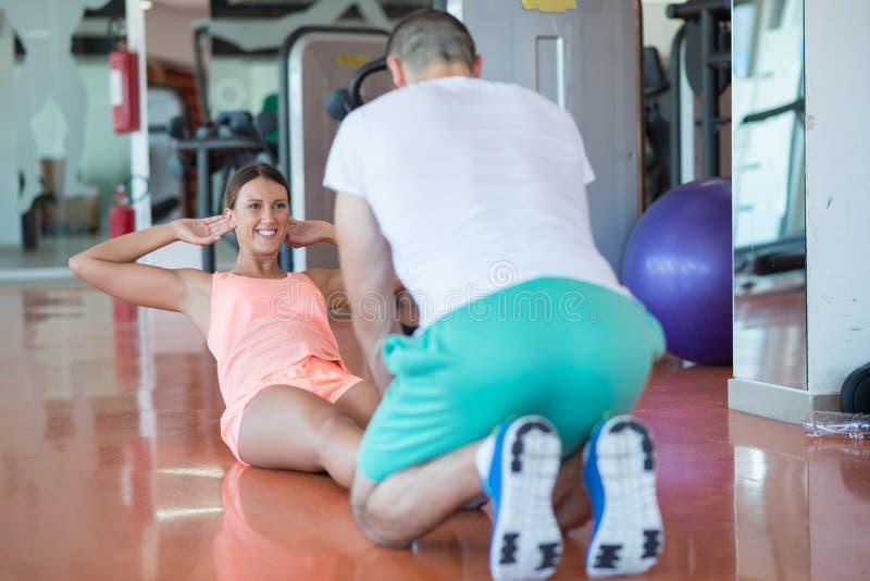训练健身房的个人教练员一名妇女与瑜伽球 免版税图库摄影
