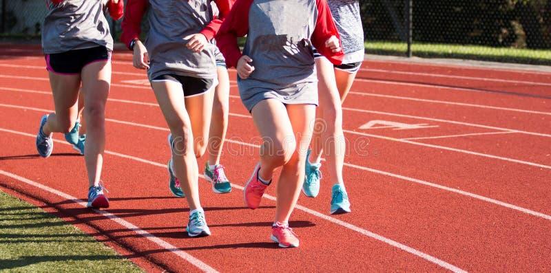 训练在一条红色轨道的小组女孩 免版税库存图片