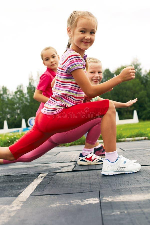 训练在体育场舒展的孩子 免版税库存照片