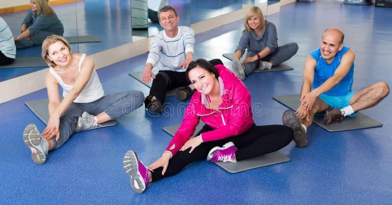 训练在体育席子的一间健身房的人们 库存照片