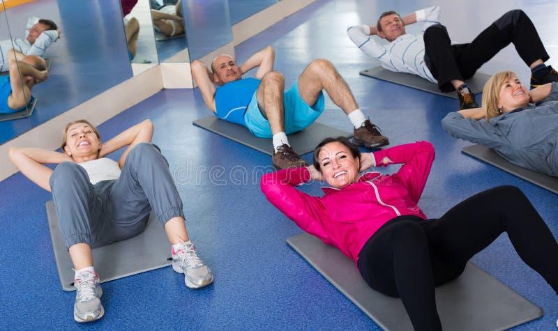 训练在体育席子的一间健身房的人们 免版税库存图片