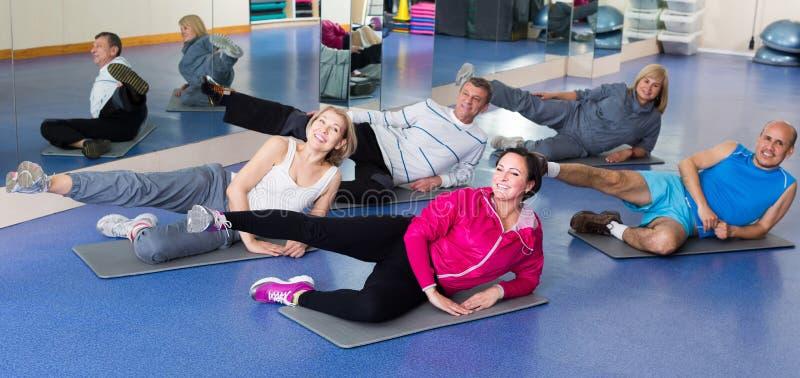 训练在体育席子的一间健身房的人们 库存图片