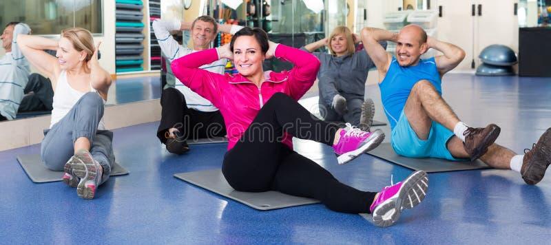 训练在体育席子的一间健身房的人们 免版税图库摄影
