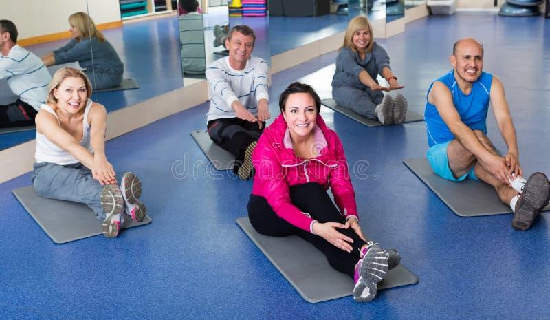 训练在体育席子的一间健身房的人们 免版税库存照片